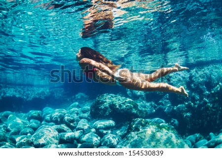 Attractive young woman floating in beautiful ethereal natural ocean pool, Underwater View - stock photo
