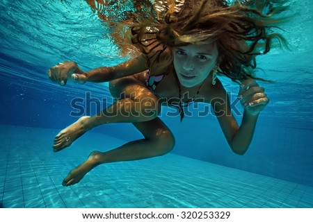 Attractive young woman floating in beautiful ethereal swimming pool - stock photo