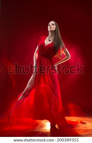 Attractive young woman full of passion standing in a red dress