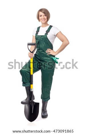 attractive young woman gardener in green workwear with shovel isolated on white background. gardening service and business concept