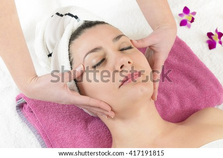Attractive young woman getting a facial massage in the beauty spa - stock photo