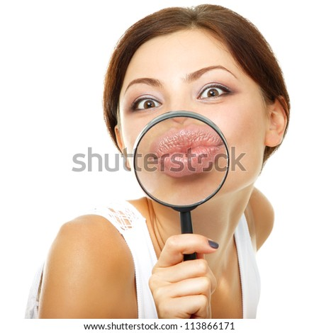 attractive young woman give kiss through a magnifying glass over white background - stock photo