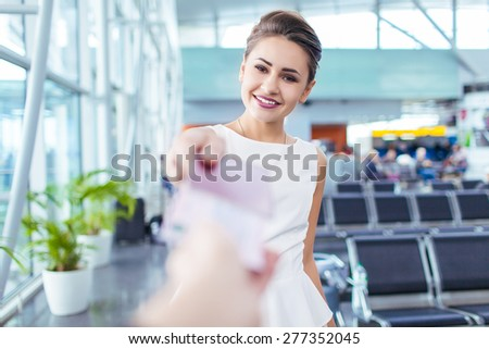 Attractive young woman giving passport and ticket at airport check-in counter - stock photo