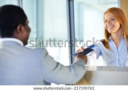 Attractive young woman giving passport and ticket back to businessman at airport check-in counter - stock photo
