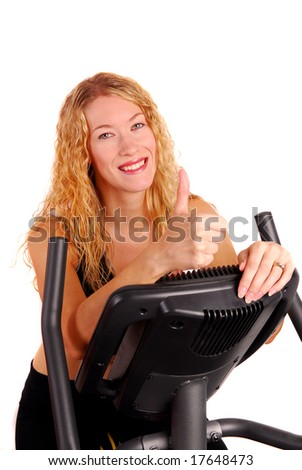 Attractive young woman giving thumbs up sign after riding an exercise bike