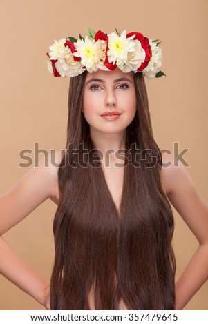 Attractive young woman has pretty long curly hair. She is standing with arms akimbo and looking at camera with confidence. The lady is wearing flower wreath and smiling. Isolated - stock photo