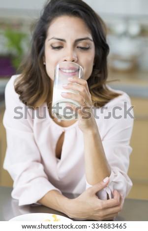 Attractive young woman having breakfast, drinking milk - stock photo