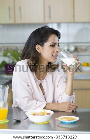 Attractive young woman having breakfast, drinking milk - stock photo