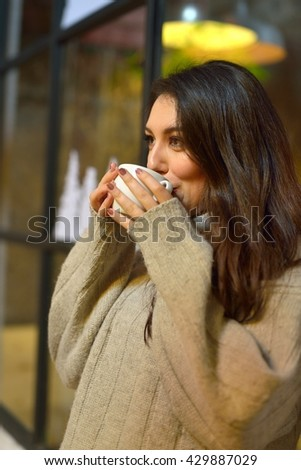 attractive young woman having coffee in the window