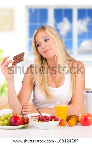 Attractive young woman having healthy or unhealthy decision of breakfast - stock photo