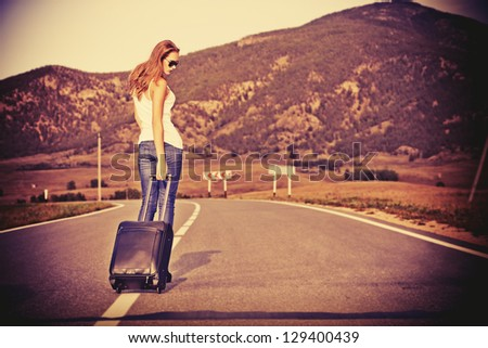 Attractive young woman hitchhiking along a road. - stock photo
