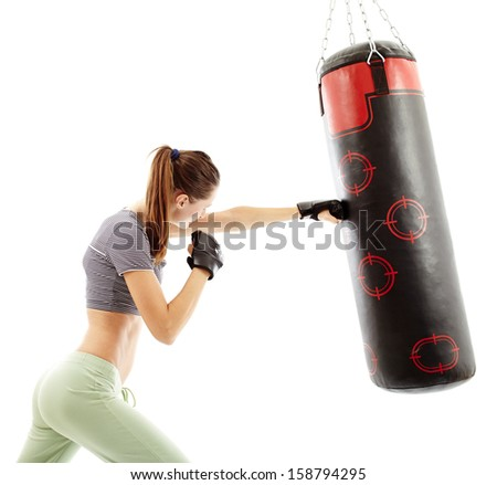 Attractive young woman hitting the punching bag isolated on white - stock photo