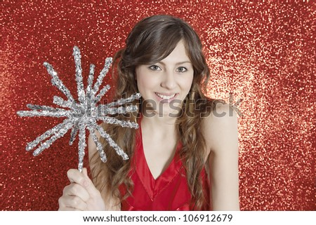 Attractive young woman holding a Christmas star against a red glitter background, smiling.