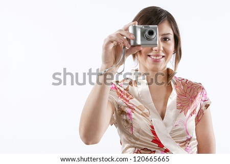 Attractive young woman holding a digital photographic camera in front of her face while standing isolated against a plain white background, smiling at the camera. - stock photo