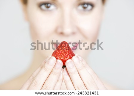 Attractive young woman holding a fresh strawberry to her lips. - stock photo
