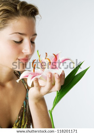 Attractive young woman holding a Japanese lilly flower in her hand, smelling it's perfume against a plain background, smiling.