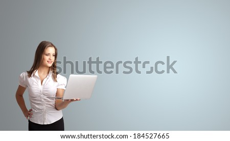 attractive young woman holding a laptop with copy space - stock photo
