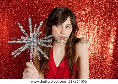 Attractive young woman holding a large christmas star while standing in front of a red glitter background with a thoughtful expression.