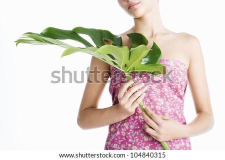 Attractive young woman holding a large green leaf in front of her while standing on a plain white background.