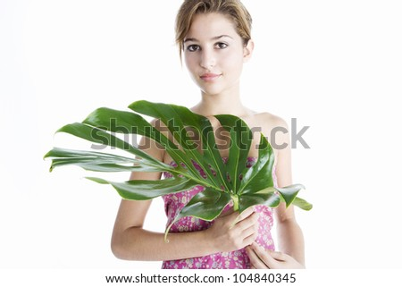 Attractive young woman holding a large green leaf in front of her while standing on a plain white background, smiling.