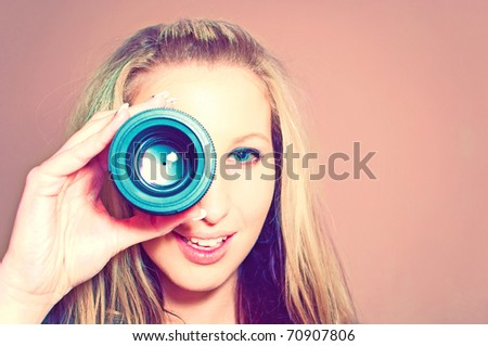 Attractive young woman holding camera lens like it was spyglass - stock photo