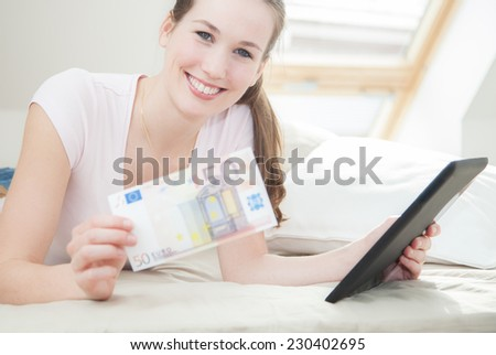 Attractive young woman holding 50 euro and tablet device - stock photo