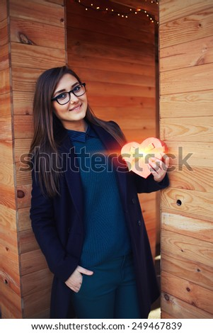 Attractive young woman holding heart shaped gift box given on Valentine's Day - stock photo