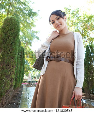 Attractive young woman holding her shopping bags while standing near a fountain in a botanic garden, outdoors. - stock photo