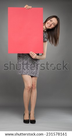 Attractive young woman holding red poster on gray background - stock photo