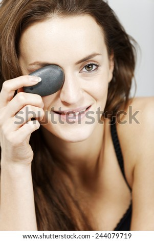 Attractive young woman holding spa treatment warm stones relaxing on a bed in black underwear