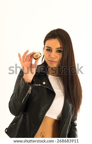 Attractive young woman holding sushi in her hand - interesting Asian-Caucasian mix with sexy clothes and pierced bellybutton on bright background - stock photo