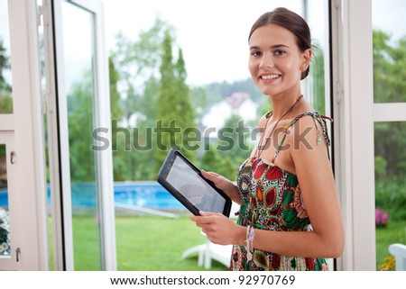 Attractive young woman holding tablet pc - stock photo