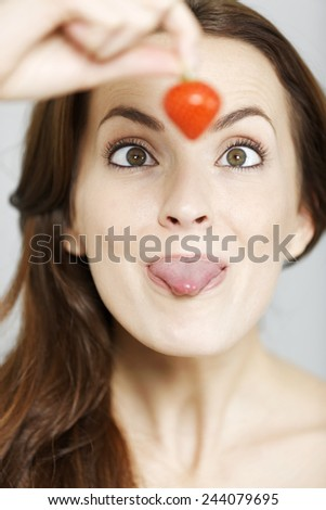 Attractive young woman holding up a strawberry and looking at it before eating - stock photo