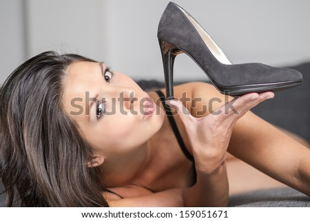 Attractive young woman holding up an elegant high heeled black ladies court shoe in a plush finish, close up of her face and the shoe