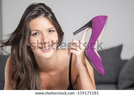 Attractive young woman holding up an elegant high heeled purple ladies high heels shoe in a plush finish, beauty and fashion concept - stock photo