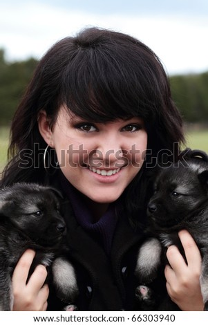 Attractive young woman holds two adorable purebred Norweigian Elkhound puppies. - stock photo