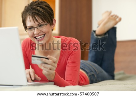 Attractive young woman holds up the credit card she is using to shop with on her laptop computer. Horizontal shot. - stock photo