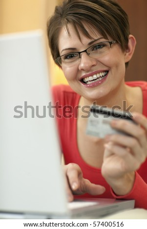 Attractive young woman holds up the credit card she is using to shop with on her laptop computer. Vertical shot. - stock photo
