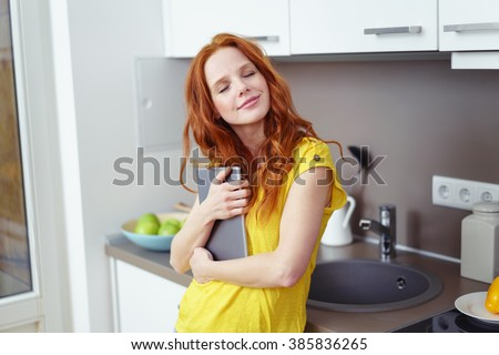 Attractive young woman hugging her tablet computer with her eyes closed and a blissful happy smile as she leans against the sink in her kitchenette at home - stock photo