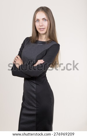 Attractive young woman in a black dress crossing her hands looking at camera. - stock photo