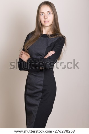 Attractive young woman in a black dress looking at camera. hands crossed - stock photo