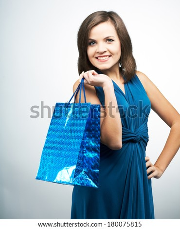 Attractive young woman in a blue dress. Holds a gift bag. On a gray background - stock photo