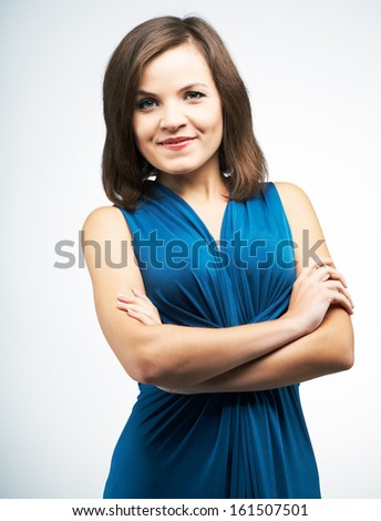 Attractive young woman in a blue dress. Standing with folded hands. On a gray background