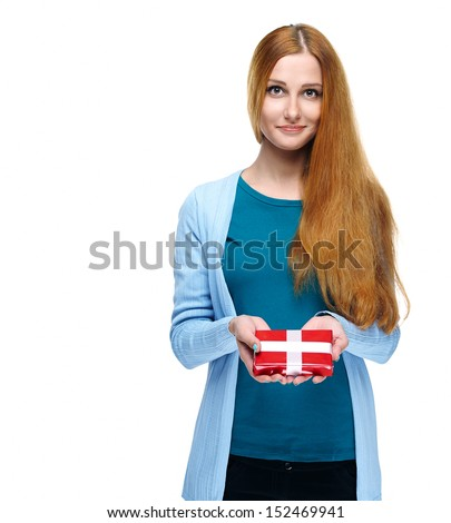 Attractive young woman in a blue shirt. Holds a gift box. Isolated on white background