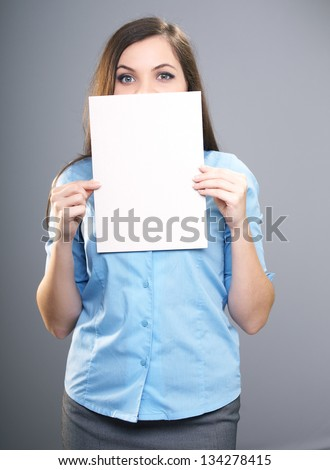 Attractive young woman in a blue shirt. Woman holds a poster and covers her face. On a gray background - stock photo