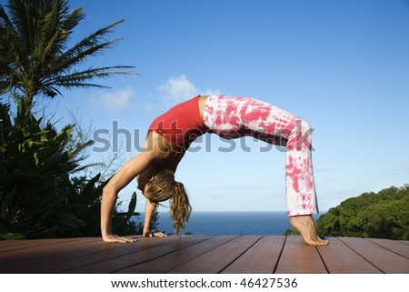 Attractive young woman in a bow position doing yoga on a deck with the ocean in the background. Horizontal shot. - stock photo
