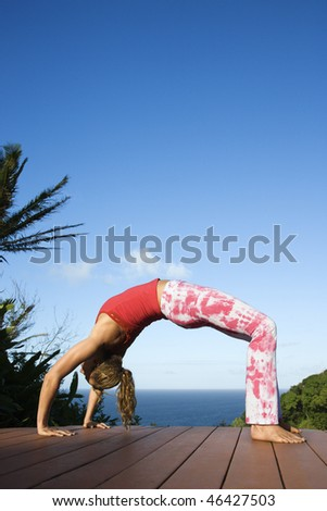 Attractive young woman in a bow position while doing yoga on a deck with the ocean in the background. Vertical shot. - stock photo