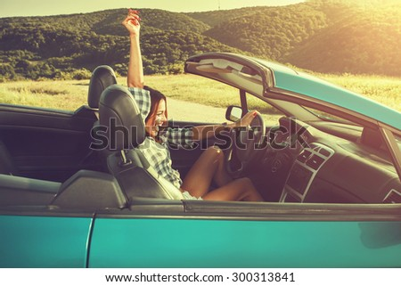 Attractive young woman in a convertible. Selective focus on face - stock photo