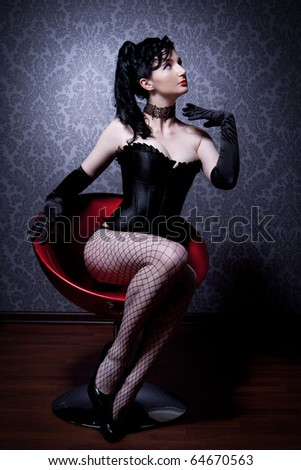 Attractive young woman in a corset is sitting on a chair and looks into the camera - stock photo