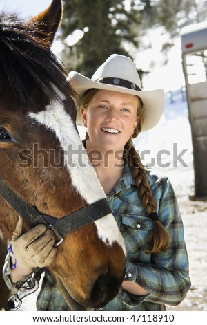 Attractive young woman in a cowboy hat, holding a horse and smiling. Vertical shot. - stock photo